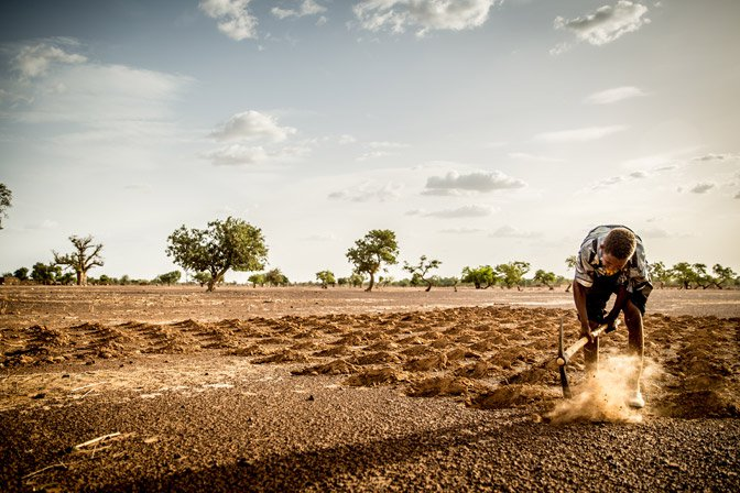 Een boer bewerkt zijn grond in Burkina Faso © Thomas De Boever/Broederlijk Delen