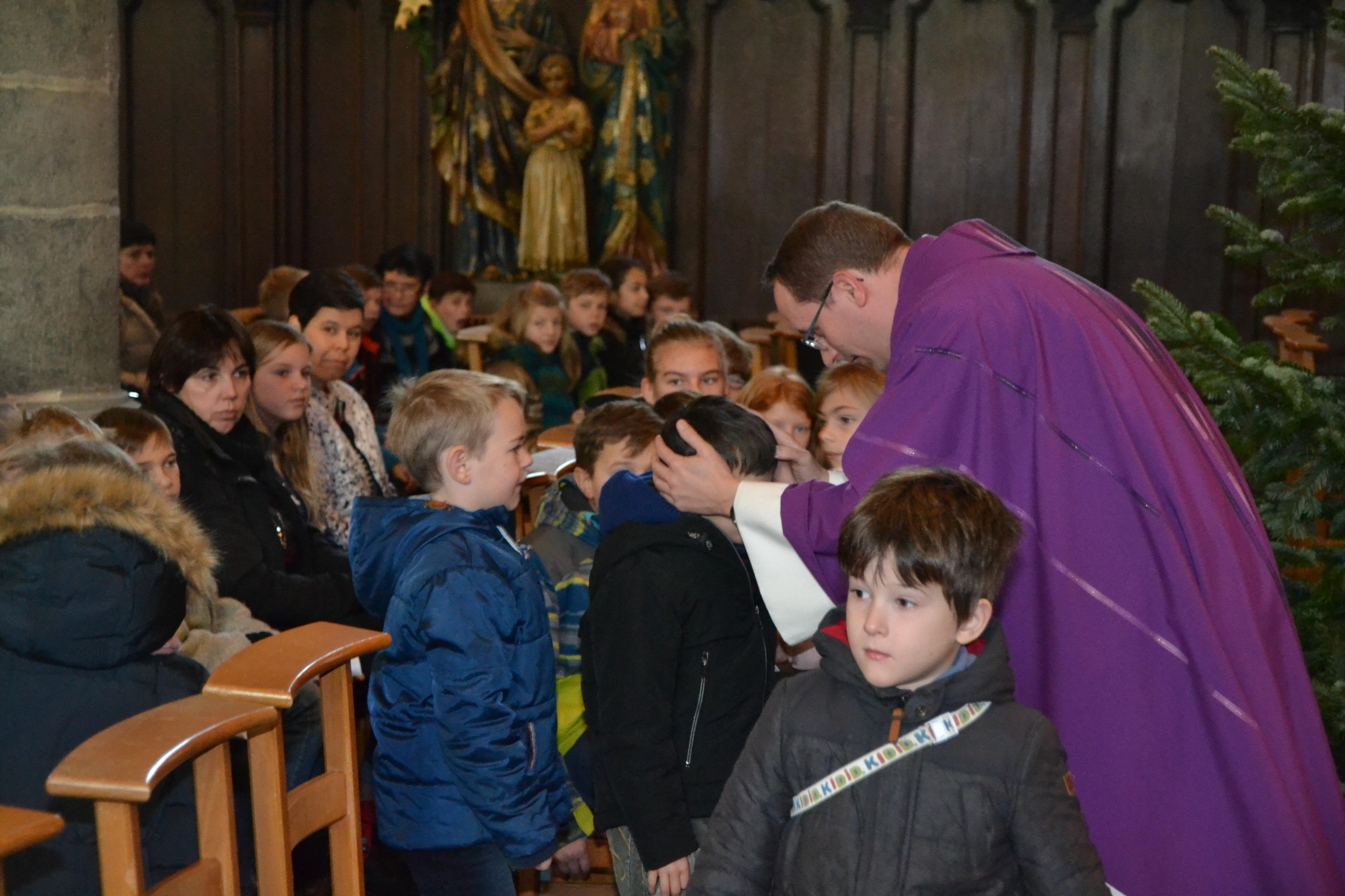 Kinderen die nog geen communie mogen ontvangen, krijgen een kruisje. © Geert Defauw