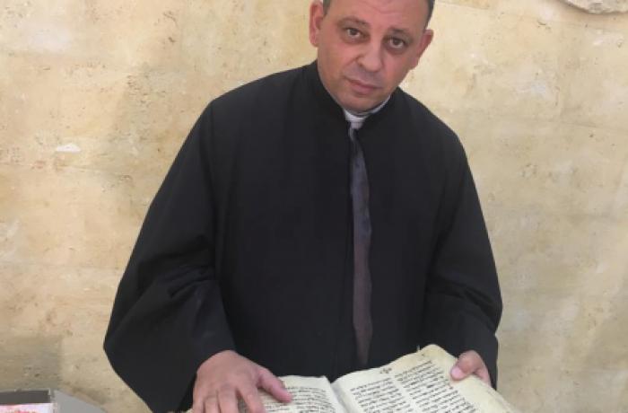 De pastoor van Erbil neemt ontroerd de oude kerkboeken in ontvangst van het islamitische gezin dat ze onder IS bewaarde.  © Asianews