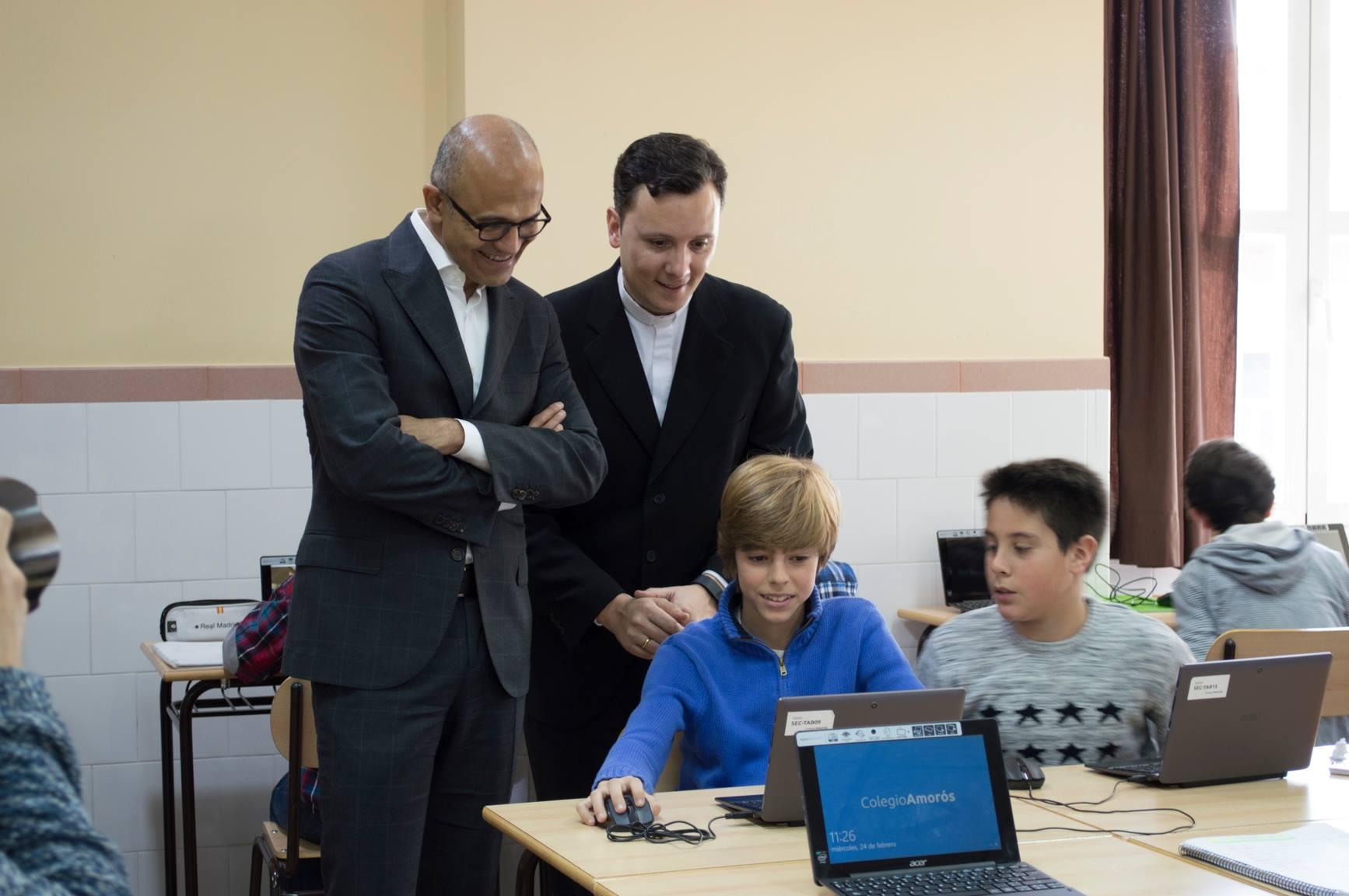 Microsoft-CEO Nadella (l.) kijkt toe hoe een leerling met Minecraft werkt.