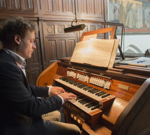 Organist Emmanuel Van Kerckhoven aan de speeltafel van het Loret-orgel in de Antwerpse Sint-Norbertuskerk © Ilse Prinsen