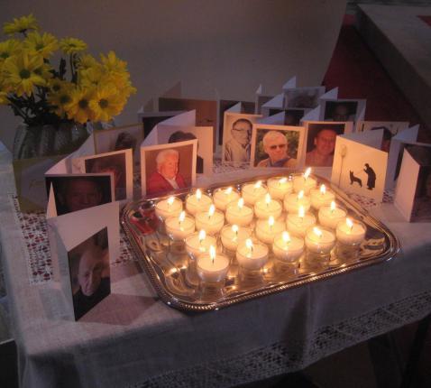 De kruisjes die bij de uitvaart op de kist of bij de urne lagen, brachten we naar voren en we brandden een kaarsje voor deze overledenen: ze gaan niet uit onze gedachten! © L.J.