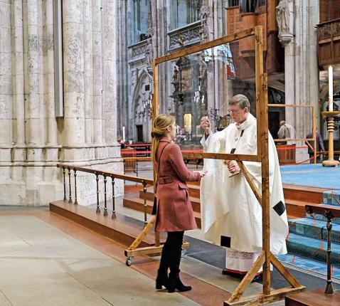Uitreiking van de communie in de Dom van Keulen, voortaan achter plexiglas.  © KNA-Bild