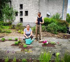 Hildegart Uvin en Johan aan het werk in de stiltetuin Hemelse Gaarde in Erembodegem.