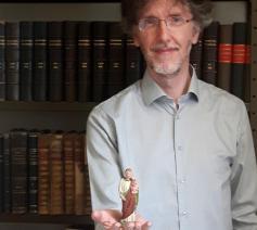 Archivaris Gerrit Vanden Bosch met een beeldje van de heilige Antonius van Padua, patroon van verloren voorwerpen. 'Komt altijd van pas wanneer we een stuk niet vinden in het archief!' © Gerrit Vanden Bosch