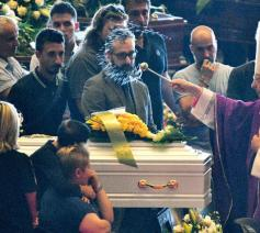 Kardinaal Angelo Bagnasco besprenkelt de kist van een van de slachtoffers © VaticanMedia