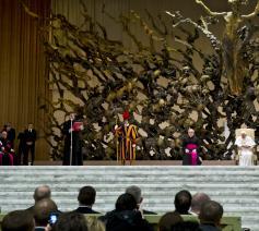 Het sculptuur domineert het podium van de Paulus VI-aula. Hier een foto uit januari 2013 met paus Benedictus XVI.  © Wikimedia