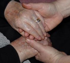 Twee paar handen houden elkaar vast en vormen een kruis… (© RR)