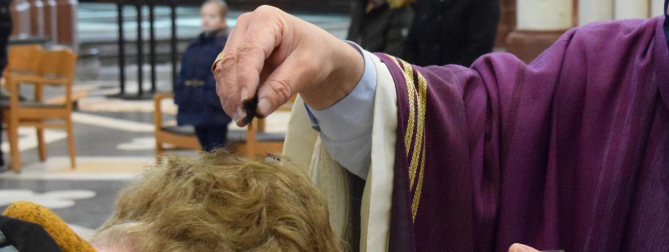 Bisschop Lode Aerts strooit as over de kruin van een gelovige. © Michiel Van Mulders