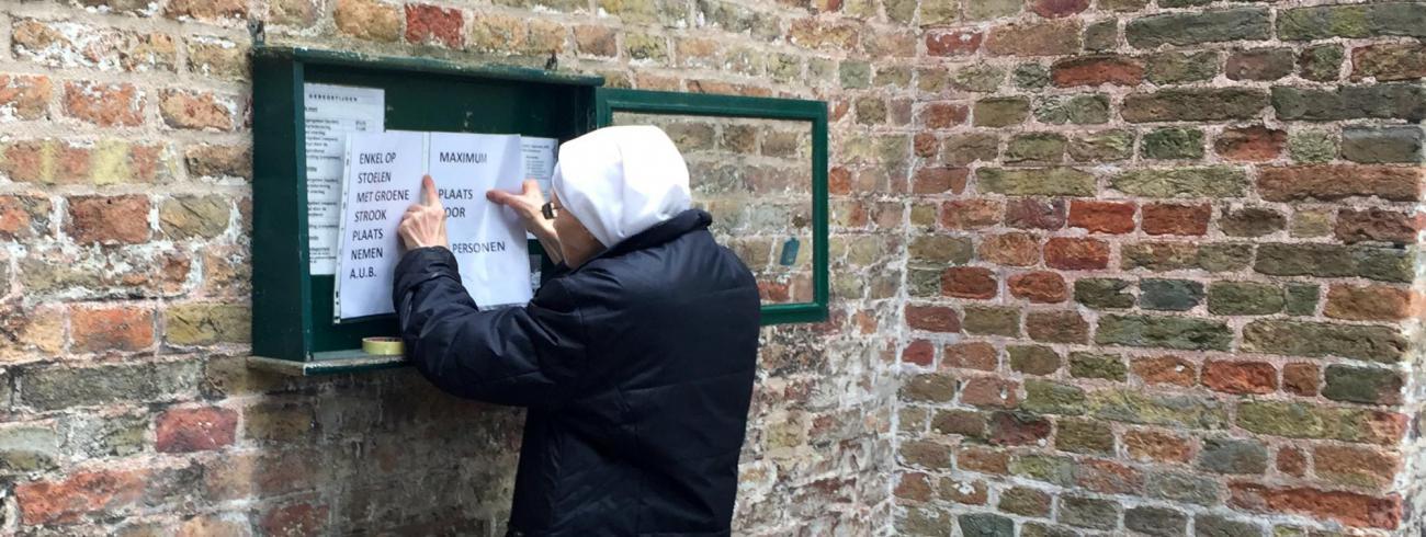 Een zuster hangt een blad met richtlijnen uit aan de Begijnhofkerk in Brugge. © Lieve Wouters