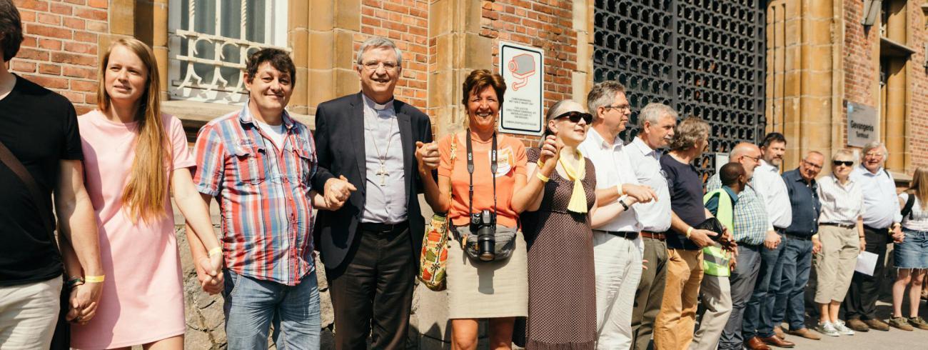 Aalmoezenier Donatienne de Borman en bisschop Bonny omarmen met vele anderen de gevangenis van Turnhout. © Mathias Hannes