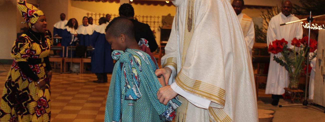 Een kind brengt Gods Woord naar binnen tijdens de viering van Afrikadag in de Antwerpse Sint-Walburgiskerk © Passy Chebe