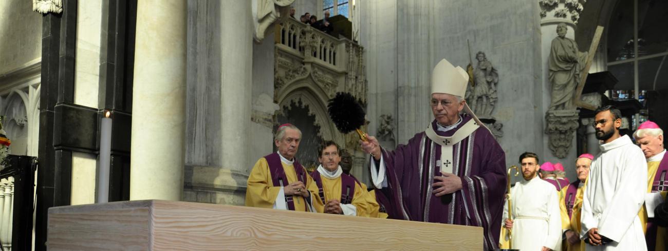 Kardinaal De Kesel besprenkelt de kist ten afscheid. 'Wij vertrouwen Godfried aan uw vaderlijke liefde in wie hij zijn vertrouwen stelde. Wij zijn U dankbaar voor al het goede dat Gij ons door hem gaf en waardoor hij blijvend teken is van uw Liefde.' © Hellen Mardaga