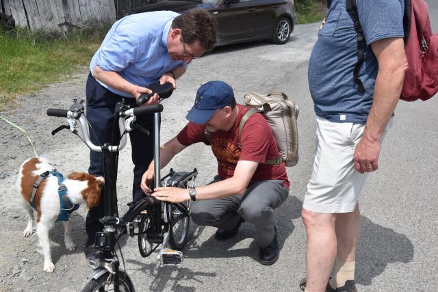 Een wandelaar verhelpt een mechanisch probleem aan de bisschoppelijke fiets. © PDL