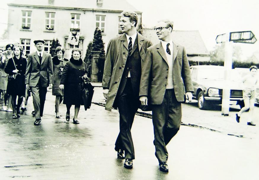De nieuw-gewijden priesters Luc Van Looy en Aloïs Vissers wandelen door Tielen na hun eremis © privé-archief Luc Van Looy