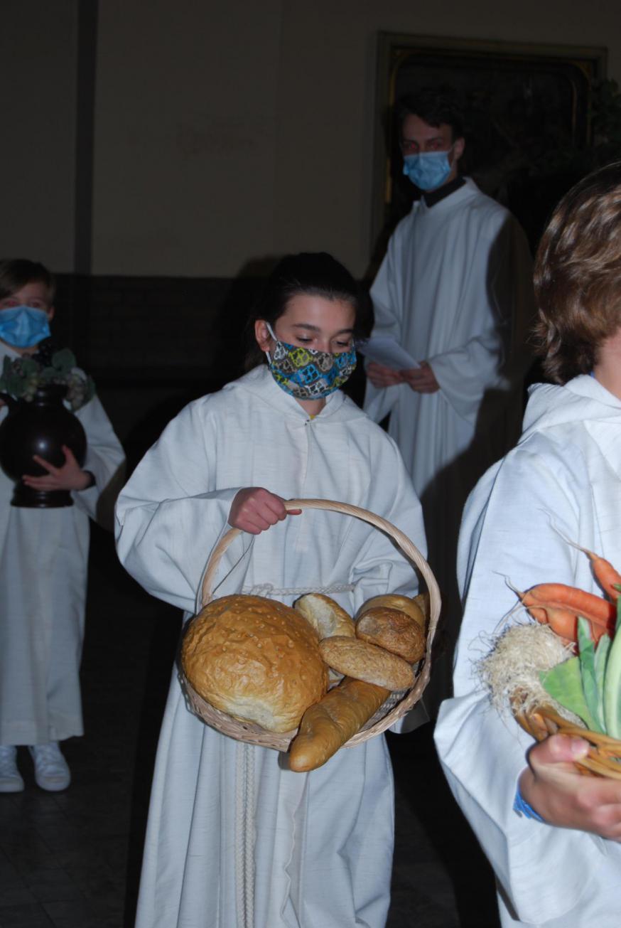 Misdienaar Mats bracht een grote korf met vruchten aan en misdienaar Selena zorgde voor het brood, met veel dank aan bakker Gregory.  © D.D.