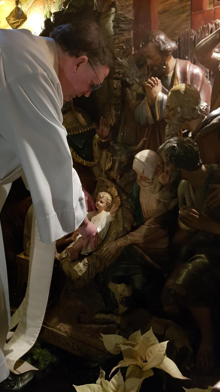 Priester Dick ligt het kerstekindje in de kerststal.  © Claraparochie