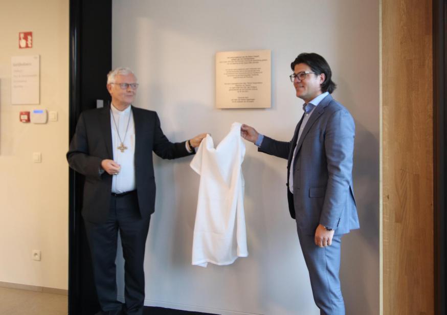 Mgr. Hoogmartens en gedeputeerde Igor Philtjens onthullen de gedenkplaat aan de ingang. © Jente Vandewijer