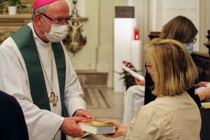 Hulpbisschop Vanhoutte overhandigt de Bijbel en aanstellingsbrief. © Laurens Vangeel