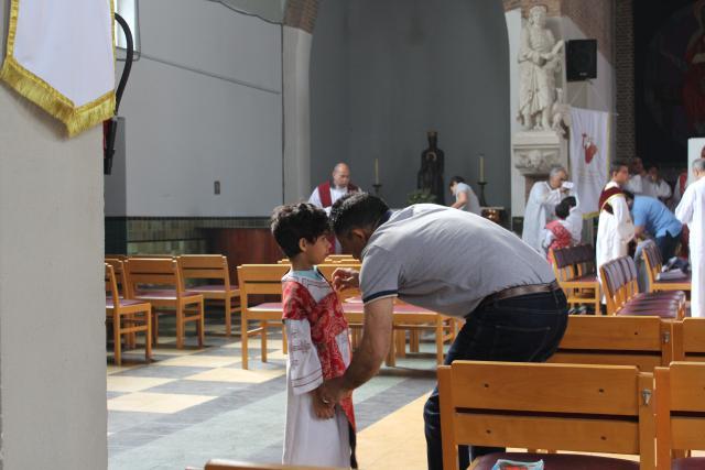 De papa helpt de misdienaar bij het aankleden © JvR