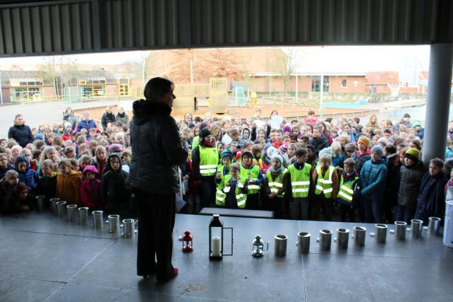 De burgemeester spreekt de kinderen van de Gemeentelijke Basisschool toe. Voor elke klas staat een kandelaar klaar. © Guido Dumon