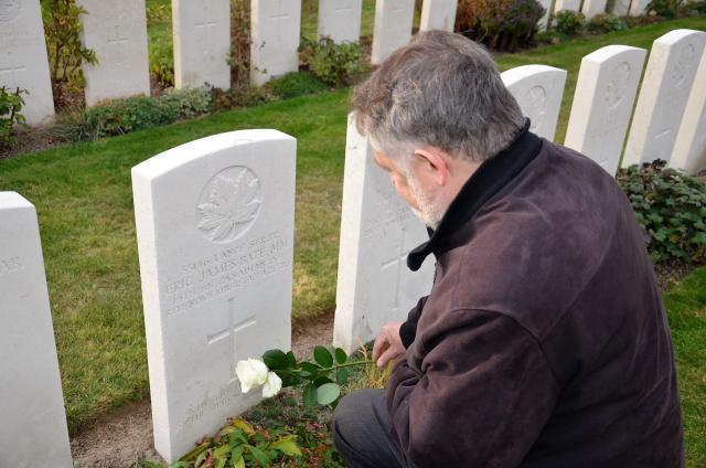 Mgr. Jean Kockerols legt een roos neer bij het graf van Eric James Bate op Tyne Cot © Hellen Mardaga