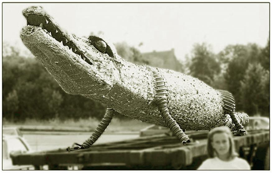 De krokodil, 10,80 m lang, bestaat uit 450 kg afval. Door vuilnis te recycleren tot kunst, door de amorfe afvalstroom uit de Pandoradoos van de technologie aan vorm te ontwerpen.