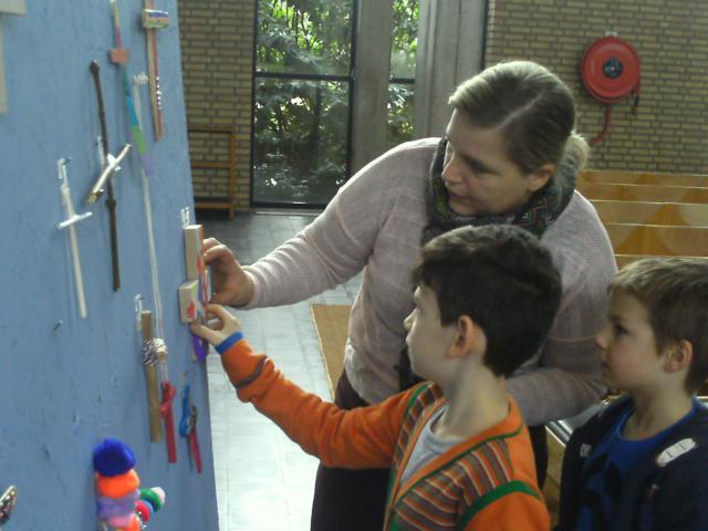 De kruisjes die de kinderen thuis geknutseld hebben worden op het grote bord gehangen