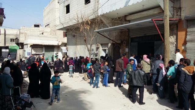 Een lange rij wachtenden bij de voedselbedeling van Caritas. © mgr. Johan Bonny