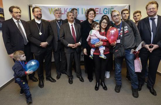 De Syrische vluchtelingegezinnen met vertegenwoordigers van de erkende erediensten en de Sint-Egidiusgemeenschap © Belga