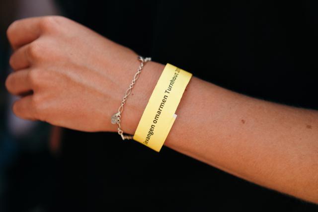 Het gele armbandje verwijst naar het themalied, over een geliefde die een geel draadje aan een oude eik hangt als teken van verbondenheid. © Mathias Hannes