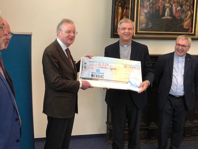 Mgr. Johan Bonny overhandigde een cheque van 3.555 euro aan Frank De Coninck, voorzitter van Caritas International, en François Cornet, directeur-generaal van Caritas International, ter ondersteuning van het werk van Caritas in Syrië © Toon Osaer