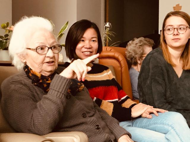 In de woonkamer zitten enkele ouderen gezellig bijeen. Ina en Pat schuiven mee in de fauteuil.  © Lieve Wouters