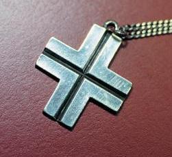Het kruisje, gedragen door de zusters bernardinnen. De bleke achtergrond met daarin het zwarte kruisje verwijst naar het wit-zwarte habijt van de cisterciënzers en hun eeuwenlange verbondenheid met deze spirituele traditie. © zrs bernardinnen