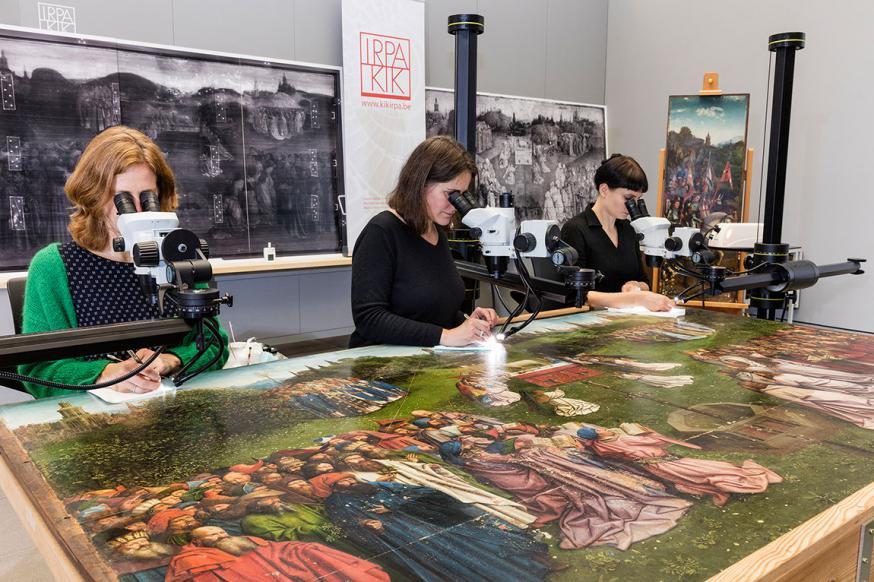 Restaurateurs van het Lam Gods aan het werk met stereomicroscoop en chirurgisch scalpel © Sint-Baafskathedraal Gent, Lukasweb.be-Art in Flanders vzw, foto KIK-IRPA