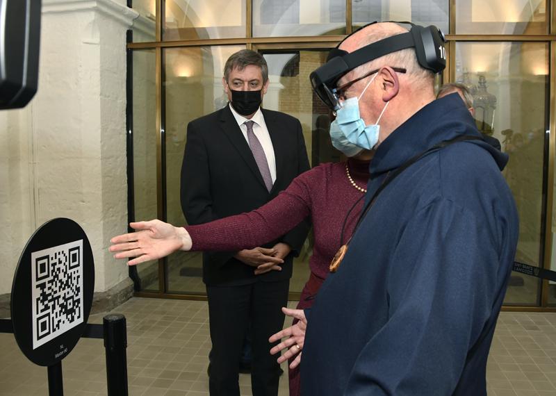Bisschop Lode krijgt uitleg bij het gebruik van de 'augmented reality''bril. © Firmin De Maitre