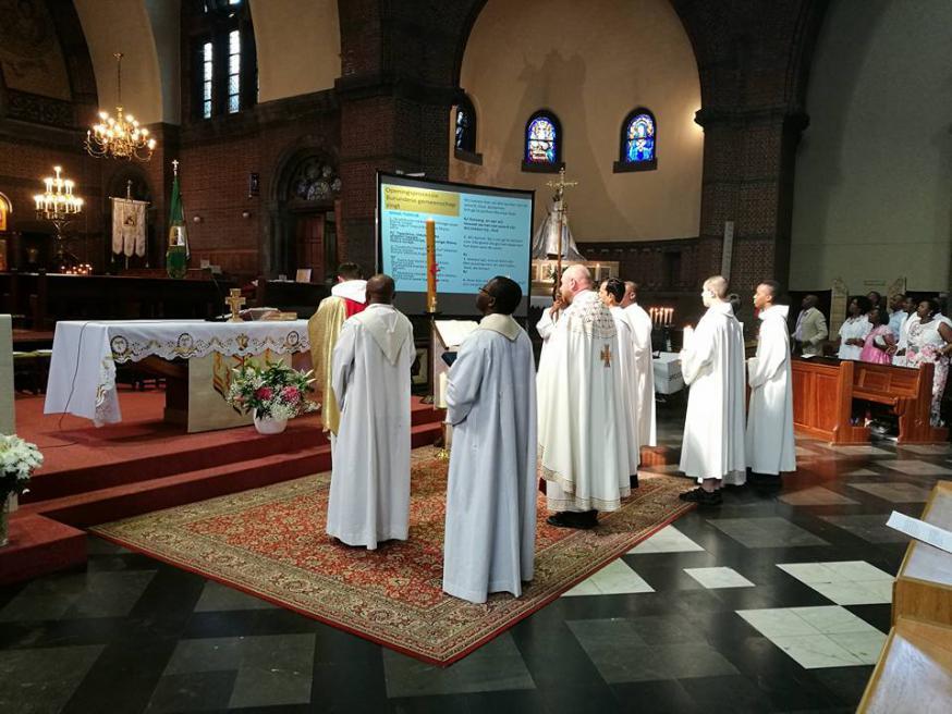 Priesters voor het altaar bij intrede