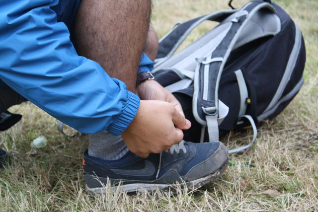 Yassine van ons Dapperevoetjesteam bindt zijn schoenen vast.