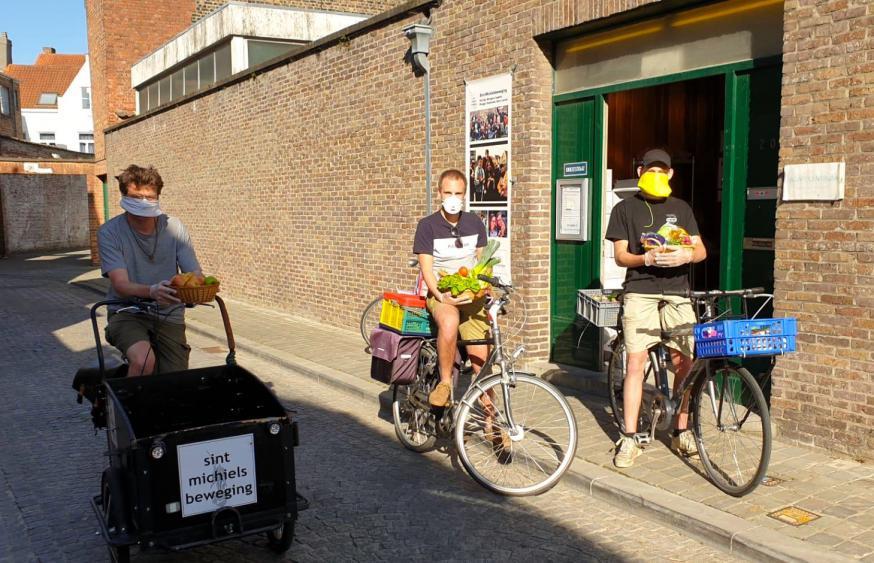 Voedselbedeling door jongeren van de Sint-Michielsbeweging in Brugge. Priester Lode Vandeputte op de fiets. © Sint-Michielsbeweging